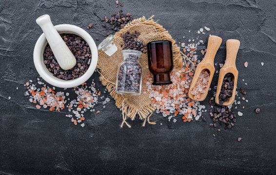 Himalayan black salt and Himalayan pink salt on dark concrete background. Himalayan salt commonly used in cooking and for bath products such as bath salts.