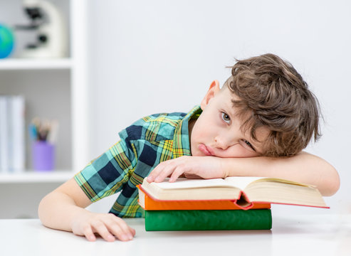 Lazy boy lies on the books at a school
