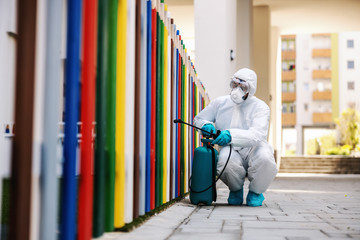 Man in sterile uniform and mask sterilizing fence of kindergarten from covid-19 / corona virus.
