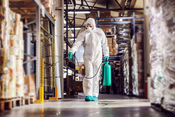 Man in protective suit and mask disinfecting warehouse full of food products from corona virus /...