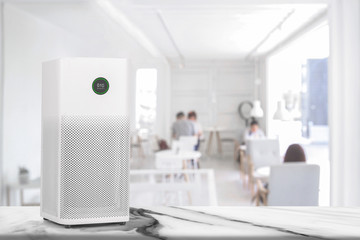 Air purifier in white workplace room with filter for cleaner removing fine dust PM2.5