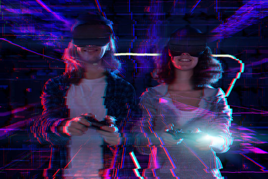 Closeup hands are holding wireless controllers joysticks. Boy and girl are playing in virtual reality game club. Friends in VR glasses are gaming. Entertainment and leisure concept. Modern technology.