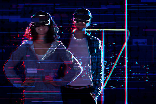 Friends ready to play in virtual reality game club. Young woman and man in VR glasses are prepared for gaming with holograms in simulator strategy. Entertainment and leisure concept. Modern technology