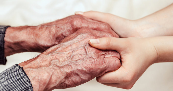 Helping hands. Care for the elderly. Young woman holding hands with a senior lady