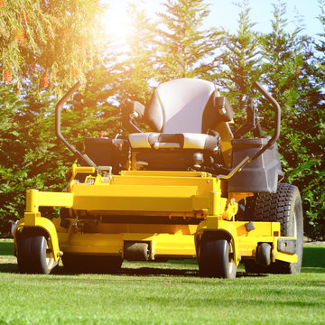 The yellow zero-turn mower parked in the middle of the green grass field, the orange sunlight splashes behind and the green background fence, mow the lawn service concept.