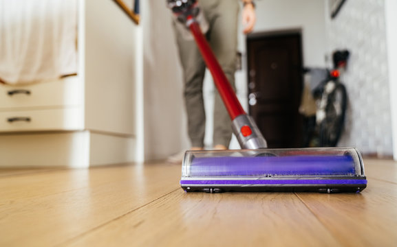 Vacuum cleaner in the hands of man. Cleaning the wooden floor in the apartment.