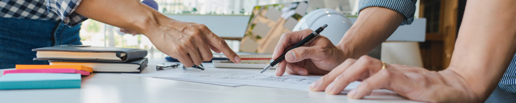 Cooperation Corporate designers in the office are working on a new project Planning blueprint Design at construction site at desk in office.
