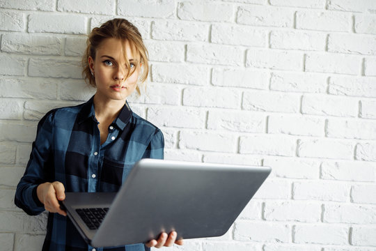 Young woman freelancer with laptop in her hands standing against white brick wall.