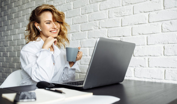 Smiling woman with curly hair sitting at table with laptop.