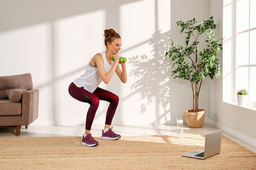 Young woman squatting with dumbbells at home.