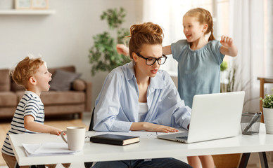 Little children distracting dedicated young woman working on laptop at home.