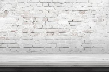 Empty white wooden table and rough brick wall
