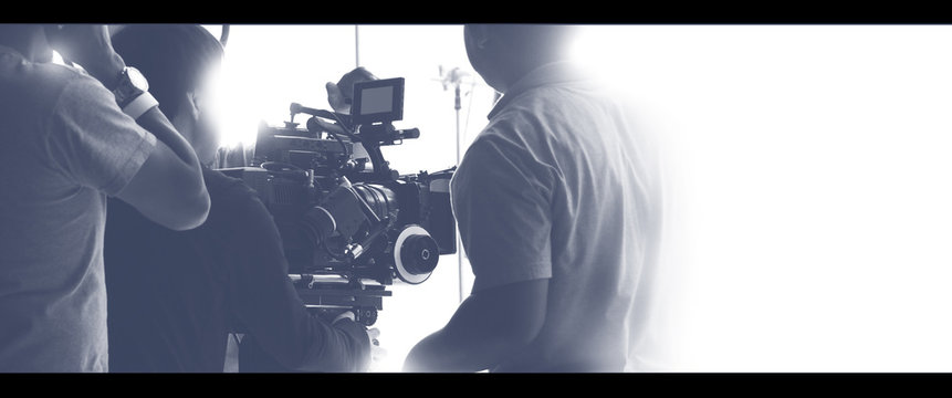 Colorful images of behind the scenes shooting production crew team and hd video camera equipment in studio which includes tripod, soft box light, monitors, lens for making film or movie or live broadc
