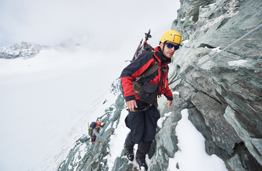 Full length of male mountaineer in sunglasses using fixed rope to climb winter mountain. Alpinist in safety helmet standing on rock covered with snow. Concept of mountaineering, alpine rock climbing.
