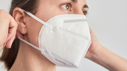 Close up picture of a brunette woman wearing a KN95 FPP2 mask.