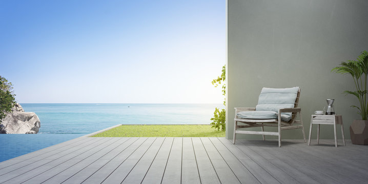 Armchair on terrace near swimming pool and garden in modern beach house or luxury villa. Wooden deck 3d rendering with sea view.