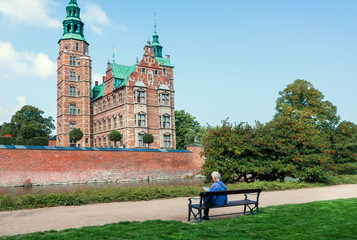 Lonely person on bench near the beautiful towers of Rosenborg Castle, built in 17th century in Copenhagen. Social distancing of people in Denmark