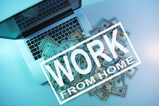 Words work from home on a  cloused silver laptop and dollars cash night online in the color light on a table night background. Top view.
