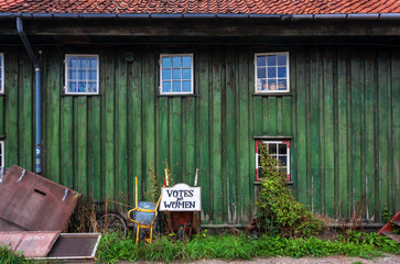 Abandones tagline Votes for Women, and wheelbarrow for worker in Christiania Freetown with wooden houses