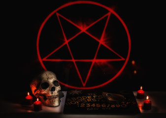 A satanic seance ritual scene with a skull, ouija board, planchette and red burning candles.