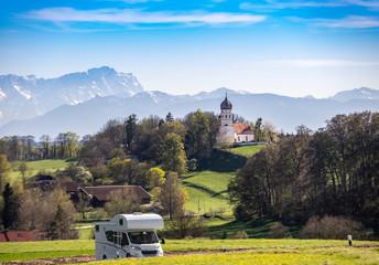 Urlaub im schönen Oberbayern: Camper fährt bei Münsing am Starnberger See - mit Panoramablick auf Kirche Alpen mit Zugspitze