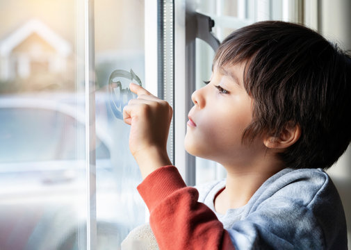 Portrait of school boy sitting next to window and using his finger drawing two hearts on window, Side view of child hand writing on glass, Toddler boy looking at him self through window.