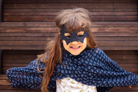 Little girl play in costume mask of scary superhero bat or batman. Childhood