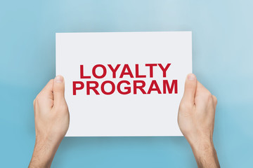 Male hands holding paper banner with words LOYALTY PROGRAM on blue background, close up. Collage