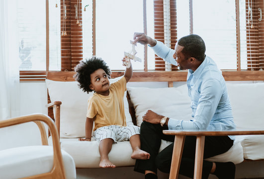 Happy family African American dad and son sitting on sofa playing with airplane wooden toy at home. Imagination dreaming of being a pilot future. Dad and Son happy family concept.
