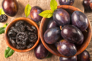 Healthy organically grown plums with dried plum fruits on a wooden rustic table