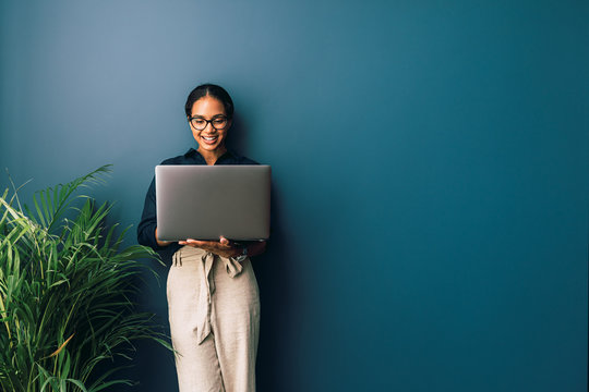 Beautiful businesswoman standing at home and holding laptop computer oh hands