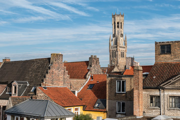 Fotomurales - View of the old town of Bruges Belgium.  Belfry tower protrudes above the typical tiled roofs.