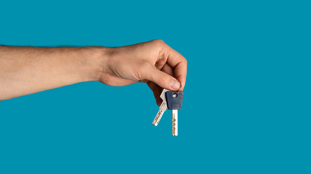 Unrecognizable young guy showing keys to new home on blue background, closeup. Blank space. Panorama