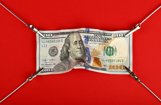 US dollar banknote stretched on red background