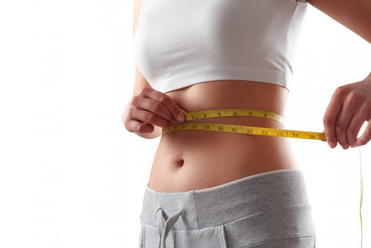 Close up of slim woman measuring her waist's size with tape measure.