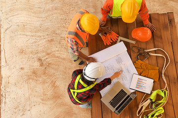 Top view of architectural engineer working on his blueprints with documents on construction site.focus on shirt engineer.Team of young man and woman engineer and architects working.