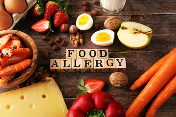 Allergy food concept. Allergy food as almonds, milk, cheese, strawberry, seeds, eggs, peanuts and .crustaceans or shrimps with wooden letter food allergy