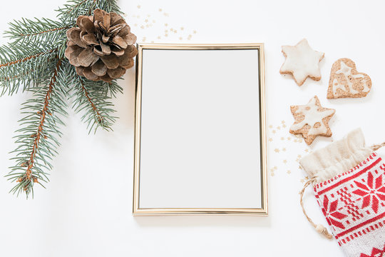 Christmas styled poster frame mockup   winter themed mockup golden frame photo   stationary winter items pine tree branch pine cone and home backed cookies   nordic design
