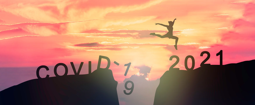 Young woman Jumping across the gap of the mountain from COVID-19 to 2021 New Year.