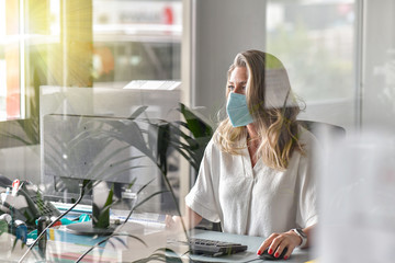 Executive woman working at her desk and wearing a protective mask against covid-19