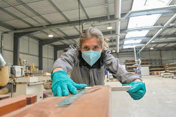 Woman worker operating in the carpentry workshop  and wearing protections againt covid-19