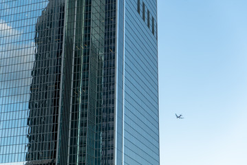 LOS ANGELES, CA, MAR 2020: passenger airliner can be seen flying in background with foreground showing part of a glass-walled skyscraper in Downtown