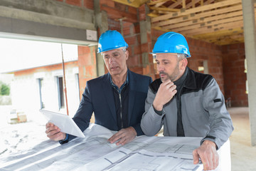 Architec and contractor checking the blue-prints on a construction site