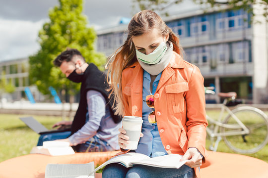 Man and woman practicing social distancing in university