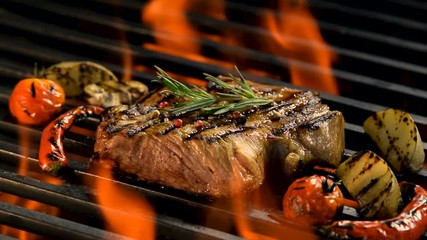 Wall Mural - Grilled pork steak with vegetable on the flaming grill .