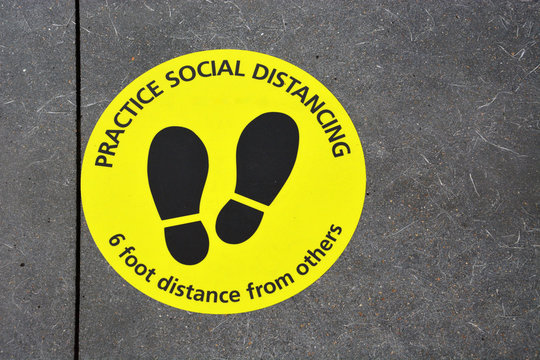 A floor sign marking off 6-feet and reminding people to social distance during the Coronavirus Covid-19 pandemic.