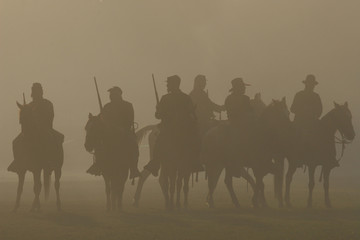 American Civil War horseback riders prepare to advance in battle. Silhouetted by a smoky haze.
