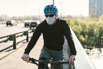 Cyclist in smog blanketed city in N95 mask. Air pollution. Industrial city. Man in mask from dust. Guy in respirator with filter pm 2.5. theme Covid 19. Smog, polluted toxic air, respiratory disease