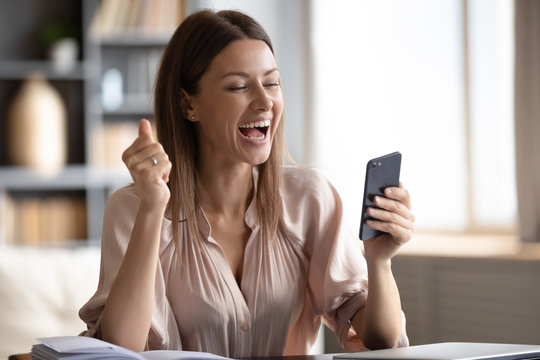 Excited happy woman looking at phone screen, celebrating online win, overjoyed young female screaming with joy, holding smartphone, reading good news in unexpected message or email