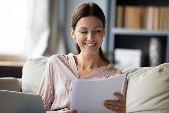 Smiling woman reading good news in paper letter close up, happy young female checking bills or documents, approved loan or credit, sitting on couch and doing paperwork or studying at home